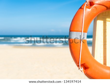 Half of orange lifebuoy in foreground. Blue clear sky, sea and sand in background. Bright sunny day. Holidays at beach. Beautiful seascape. Equipment for rescue of people. Service for lifesaving. - stock photo