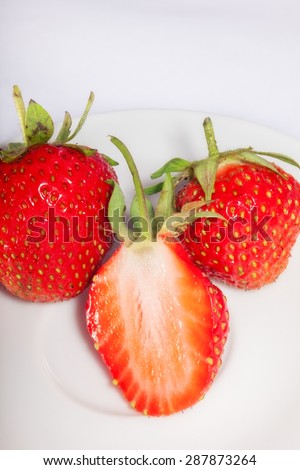 Half of ripe and juicy strawberries on a plate with two whole berries. close-up. - stock photo