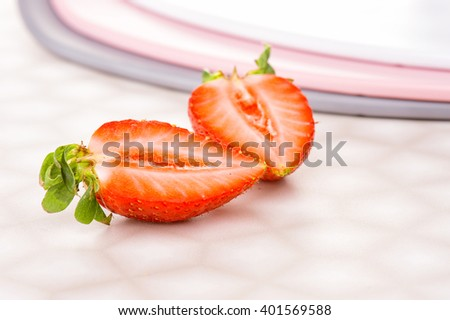 Half of succulent juicy fresh ripe red strawberry witah pink and grey plates on the decorative stone table  - stock photo