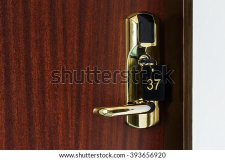 Half opened door of a room with number 37 on it. Hotel room door with lock half open. Hotel suit welcome guests. Opening door closeup. Door handle. Privacy concept. Entrance to the hotel room.  - stock photo