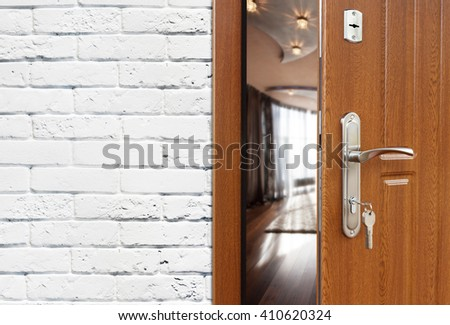 Half opened door to a living room at white brick wall, modern interior design. Handle and lock. Lounge room entrance. Welcome, privacy concept.   - stock photo
