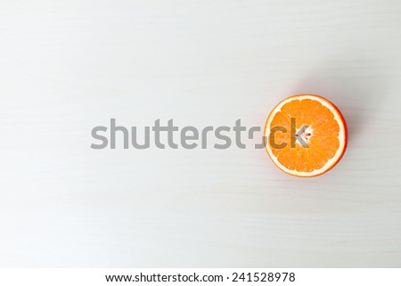 Half orange on wooden board, top view - stock photo