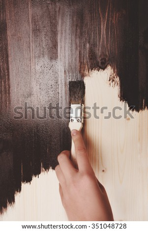Half painted wooden surface. Hand varnishing or painting natural wood with paint brush and deep brown color. - stock photo