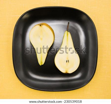half pears on black plate  - stock photo