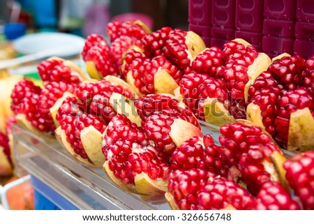 Half pomegranate and pomegranate seeds - stock photo
