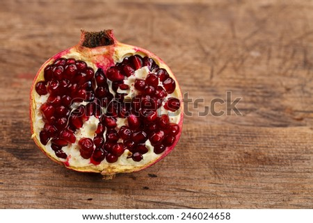 Half pomegranate on rustic wooden table - stock photo