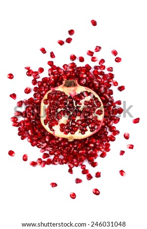 Half pomegranate surrounded with red seeds on white background - stock photo