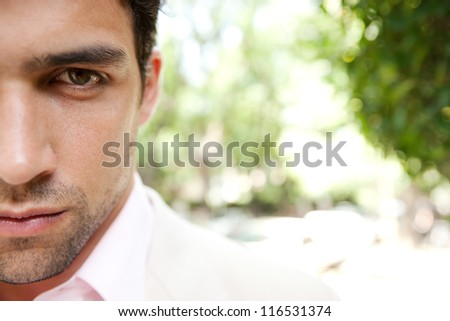 Half portrait close up of a young and attractive businessman's face looking at camera with a leafy background. - stock photo