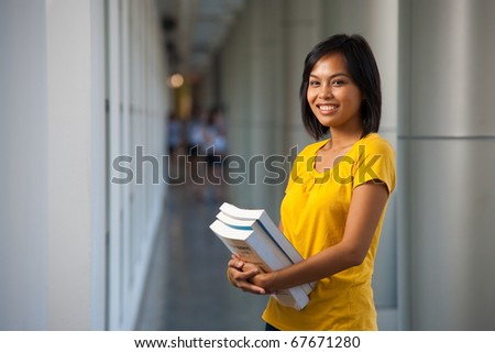 Half portrait of an adorable happy college student holding textbooks and smiling wearing yellow shirt.  Young female Asian Thai model late teens, early 20s of Chinese descent looking at camera