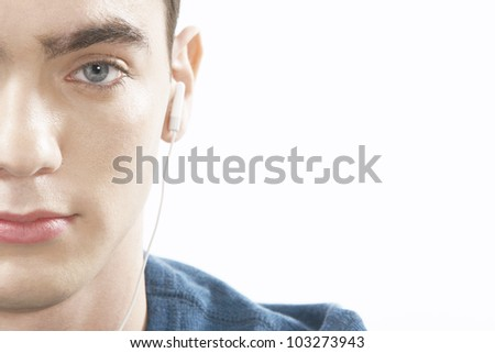 Half portrait of teenager listening to music with earphones, on a white background.