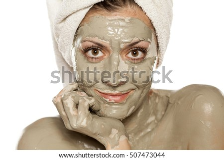 half portrait of young woman  with the green clay mask on her face
