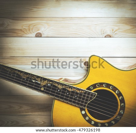 Half section of a guitar on wood with copy space