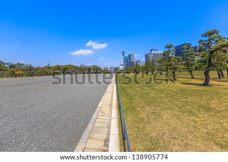 half side of street and Kokyo Gaien (Imperial Palace Outer Garden) with backgrond tokyo skyscraper and blue sky - stock photo