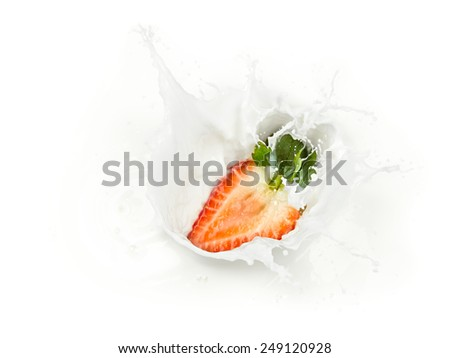 half strawberry splashes into milk - stock photo