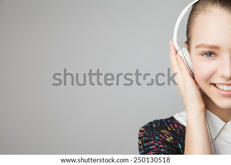 Half the face of a girl with headphones - isolated over a grey background - stock photo