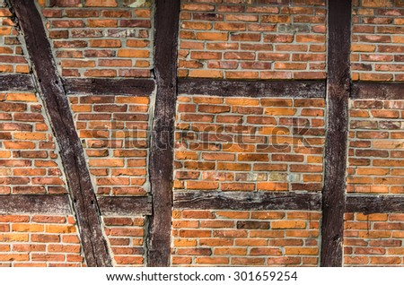 Half-timbered wall with red brick and brown wooden beams in Germany.