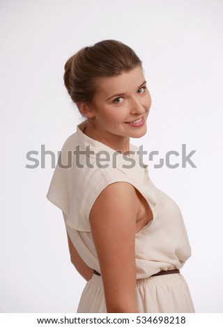 Half-turned female portrait. Young girl posing in studio on white background. She looking from the back in camera. Emotion: smiley, enjoy, fun.