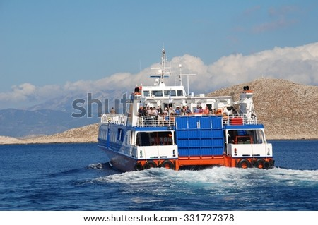 HALKI, GREECE - JUNE 9, 2015: Catamaran ferry Dodekanisos Express heads past Nissos island while departing Emborio harbour on the Greek island of Halki. The 40mtr vessel was built in Norway in 2000. - stock photo