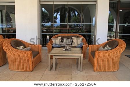 HALKIDIKI, GREECE - JULY 21, 2013: Beautiful patio with comfort rattan sofa, armchairs and pillows at summer resort, Halkidiki, Greece - stock photo