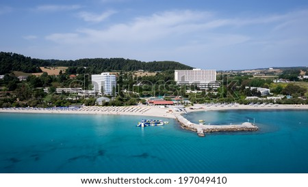 HALKIDIKI, GREECE- MAY 27, 2014: Top view of beach with tourists, sunbeds and umbrellas at a luxury hotel. Sea travel destination in Kallithea, Greece.