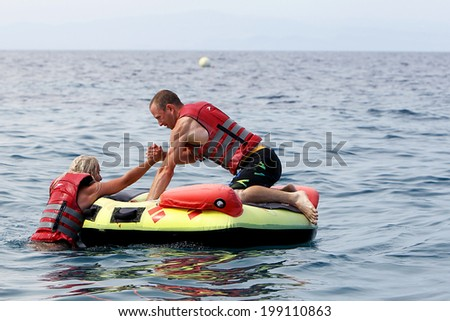 HALKIDIKI, GREECE- MAY 26, 2014: Unrecognized man helping woman to get on water inflatable. 20 million tourists expected to visit the beaches, making it a record, in Halkidiki, Greece.