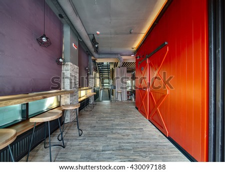 Hall in a loft style in a mexican restaurant. On the left there is a brick wall with curtained windows, wooden racks with wooden chairs near them and black wrought lamps over them. Under the racks - stock photo