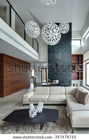 Hall in a modern style with light walls and big white round decorative lamps at the top. There is a beige sofa with pillows and plaid, dark table with three decorative vases, two black armchairs - stock photo