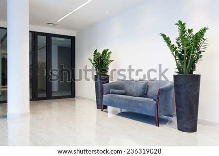 Hall with comfortable sofa in modern hotel - stock photo