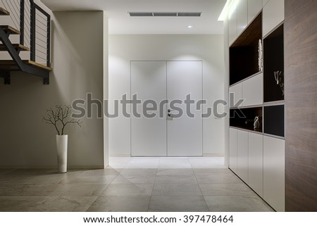 Hall with light walls and light tiles on the floor. On the left there is a part of stair and a plant without leaves in a white vase. On the right there is the wall with dark wooden niches with - stock photo