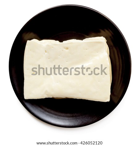 Halloumi cheese on black plate, isolated on white.  Top view.