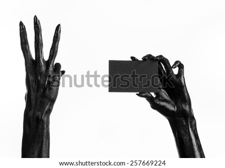 Halloween and gothic theme: The Black Hand of death holding a blank black card on white isolated background in the studio, the walking dead, change in oil prices