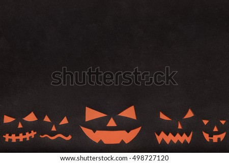Halloween background: idea is cutting paper jack o'lantern faces on black background with space for text.