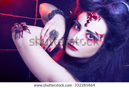 Halloween. Black widow. Young woman in dark artistic image posing with spider