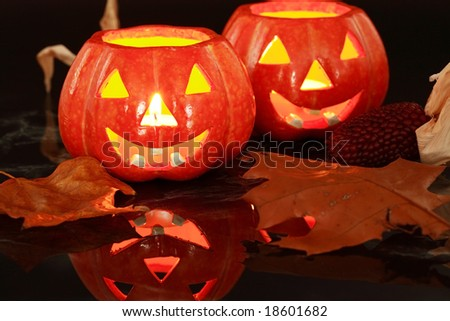 Halloween candle-light with leaves on black background - stock photo
