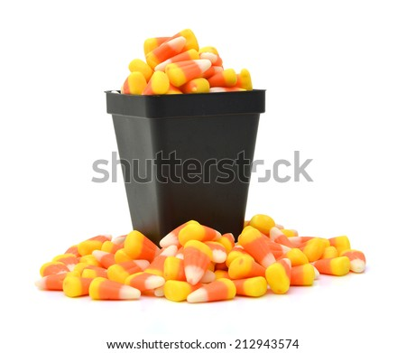 Halloween candy-corn and pumpkins overflowing the box in white background - stock photo