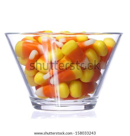 Halloween candy corn in glass bowl isolated on white background. Closeup