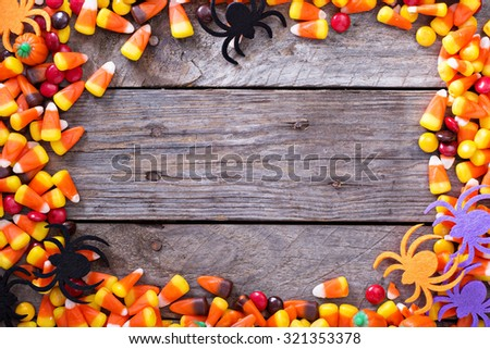 Halloween candy frame around rustic board empty space for your text - stock photo