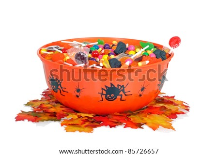 halloween candy in a bowl with fall leaves - stock photo