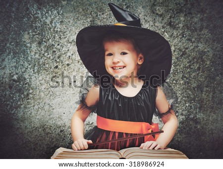 Halloween. cheerful little witch with a magic wand and the book conjure and laughs. - stock photo