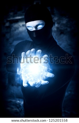 Halloween concept. Powerful Male witch or wizard with blue cold fireball in hands. Ball from frozen ice - stock photo