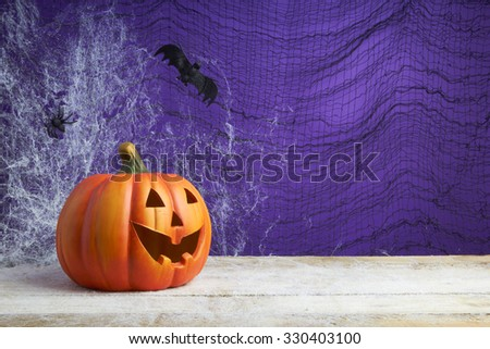 Halloween concept with a jack o lantern pumpkin, toy spider and bat on a dark cobweb background - stock photo