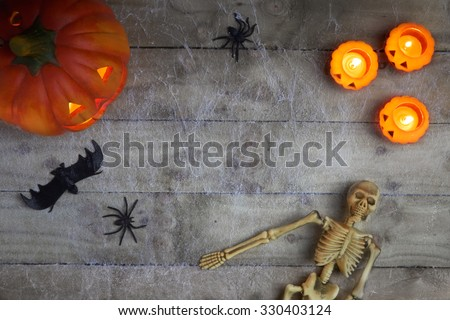 Halloween concept with a pumpkin,skeleton,candles and toy spider on a cobweb wood background - stock photo