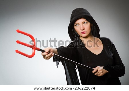 Halloween concept with woman holding pitchfork - stock photo