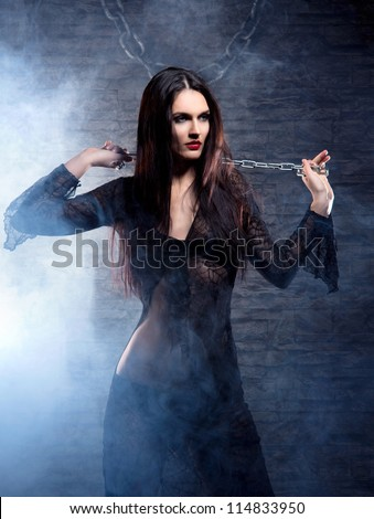 Halloween concept: young and sexy witch in the dungeon - stock photo