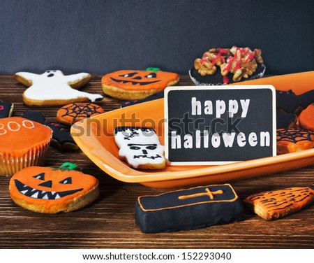 Halloween cookies on a plate orange and holiday greetings - stock photo