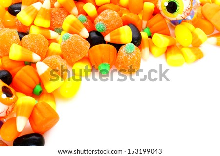 Halloween corner border of varied candies over white