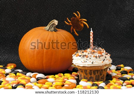 Halloween cupcake and pumpkin arranged over a dark background with scattered candies - stock photo
