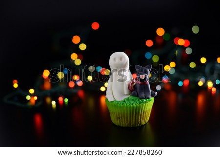 Halloween cupcake decorated with sugar ghost and black cat. Open aperture and bokeh effect. - stock photo