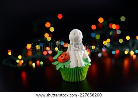 Halloween cupcake decorated with sugar ghost and pumpkin. Open aperture and bokeh effect. - stock photo