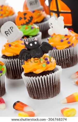 Halloween cupcake with bat, ghost, and RIP decorations surrounded by Halloween cupcakes, corn candies, and decoration. - stock photo